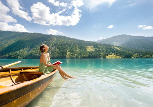 Frau genießt die Sonne im Boot auf dem Weissensee