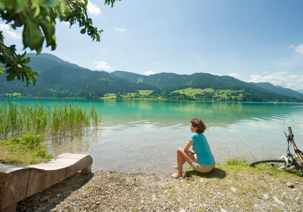 Frau sitzt am Ufer des türkisen Weissensees