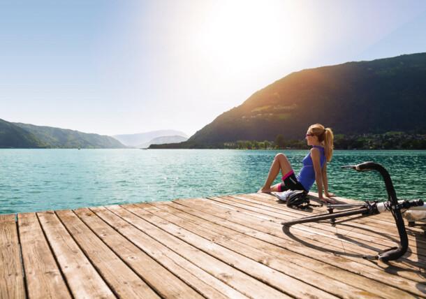 Frau lässt nach einer Radrunde die Füße in den Ossiacher See hängen