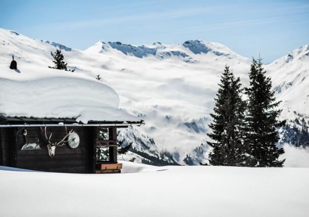 zaśnieżona chata z panoramą gór w tle, Gastein